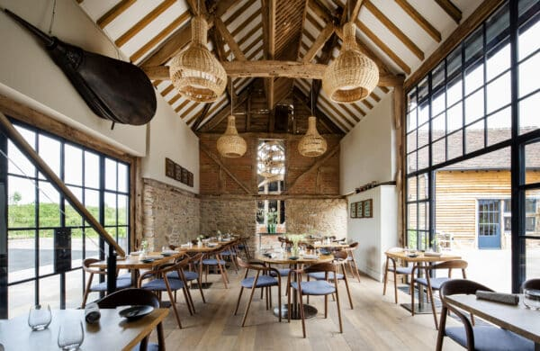 Interior of Pensons Restaurant, a barn conversion. Light-filled area interior from steel-framed windows on either side, above area exposed timber trusses with large bespoke wicker lampshades. Inside is a timber floor with seating. A modern interior with a sense of rustic charm.
