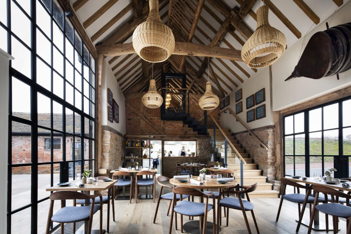 Interior of Pensons restaurant, a barn conversion. Light-Filled interior looking towards the open kitchen at the far end of the dining room.