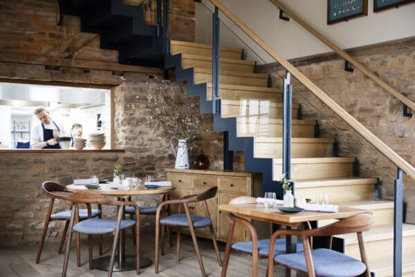 Interior of Pensons Restaurant, featuring a floating staircase made from timber and laser cut steel, a barn conversion project