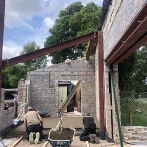 Constructing an extension. A red steel frame in the foreground and a breeze block wall in the foreground, in-between are two builders laying a screed floor.