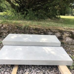 Two white stone slabs, approximately 1 foot by 2 feet, which will be laid as steps in a landscaped garden