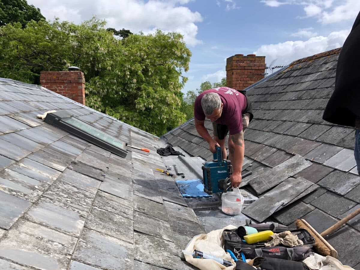 a builder working on a slate tiled roof, repairing the lead guttering on a Georgian house, listed building.
