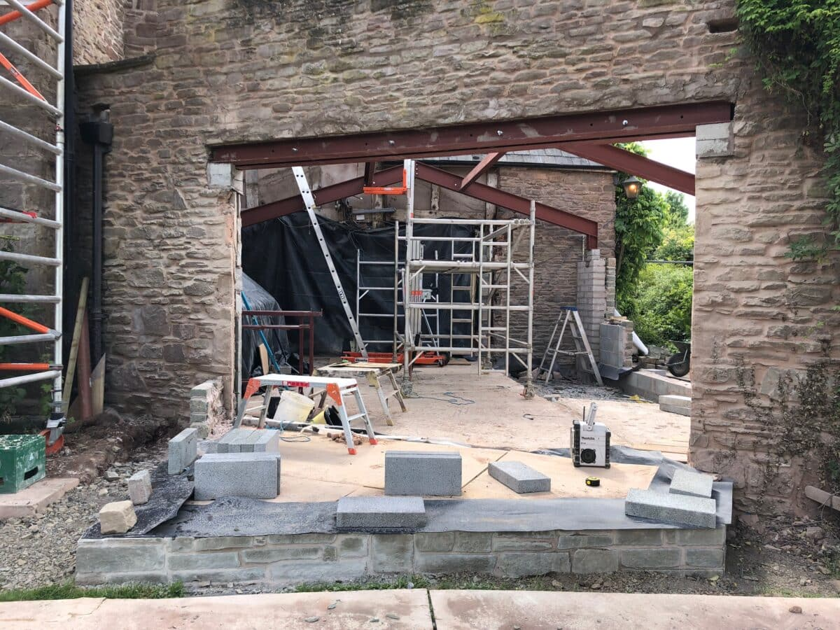 On a construction site, stone walls and steel frame work, extension to a listed building in Herefordshire, communion architects.