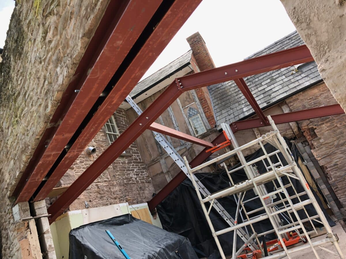 Angled photo of stone walls and supporting steel beams on a construction site for a new extension to a listed building in Herefordshire. Communion Architects.