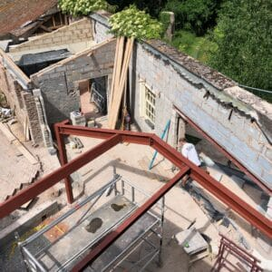 View from above, showing a red steel frame of a new extension, in the background is former extension, made from breeze blocks being reimagined.