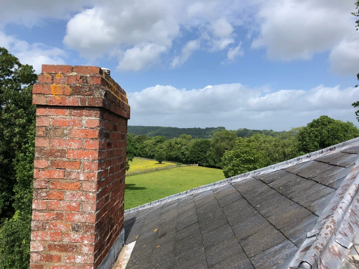 A view from the roof. A slate roof and read brick chimney in the foreground with a green field and woodland in the background. Working on a home extension to a listed Georgian building in Herefordshire. Communion Architects.