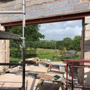 On a construction site, a breeze brick wall with a large opening in it which will form a window, through the opening can be see green fields and a woods in the background.