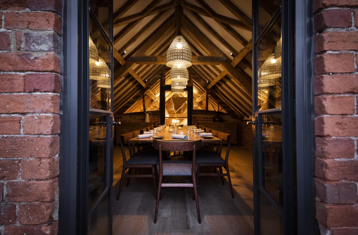 Private upstairs dining room at bensons restaurant, long central table with wood chairs along it, with an apex roof and exposed timber beams. A rustic and elegant atmosphere by candle light. Communion Architects Herefordshire