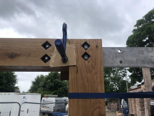 Image from construction site. The top right corner of an empty timber door frame is visible. The horizontal and vertical pieces are being temporarily held together with a joinery tools while they are secured. Through the top lintel runs a steel barn, providing extra support. Communion Architects, Herefordshire.