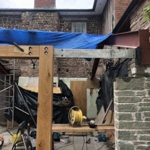 On the site of listed building in Herefordshire - constructing an extension. Image shows a low stone wall with an empty doorway frame next to it. A steel beam runs through the top timber beam proving extra support. The stone listed building can be seen in the background, communion architects Herefordshire