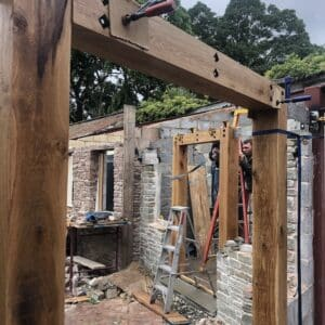On a construction site for a grade 2 listed building in Herefordshire, creation an extension. Here the construction works are securing timber doorways made of thick oak beams between breeze block walls. Communion Architects, Herefordshire