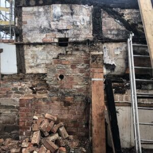 Wall from a fire damaged cottage. The timber framed walls are filled in with charred brick from the recent fire. The current structure is precarious and needs securing. Communion Architects, Herefordshire.