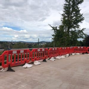 A terrace with red plastic railings around it. The view looks out over Hereford. A terrace for a garden. Communion Architects Hereford.