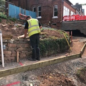 Construction worker in a hi-vis jacket measuring the level of a stone wall as part of some landscaping works in a garden in Hereford, Communion Architects