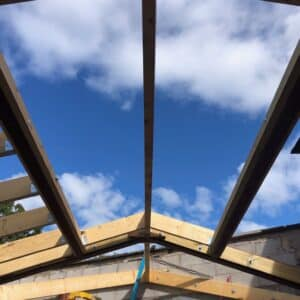 Looking towards a blue sky through a timber frame for an extension to a listed building. The gap in the roof will become a sky light. Communion Architects, Hereford