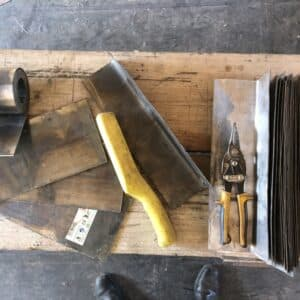 A wooden bench with lead rolls and cutting tools - part of a roofer's kit - image from a construction site in Herefordshire, communion architects