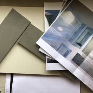 Two slender, angled tiles next to rendered bathroom plans on a workbench, planning out bathroom and tile design on site, communion architects Hereford