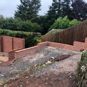 A low red brick wall in a steep garden - part of a landscaping project in Hereford - communion architects