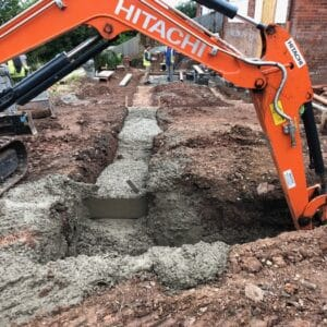 A bright orange arm of digger ploughs into the soil to create a trench for cement foundations. Communion Architects, Herefordshire