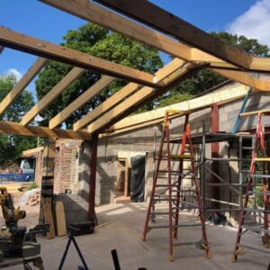 A timber frame for an extension - the blue sky and green fields can be viewed through the frame - will for a new kitchen - communion architects Hereford
