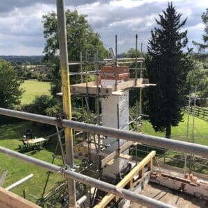 Looking across out over green field, evergreens and a cloudy blue sky from the roof of a fire damaged cottage, the view is interrupted in the foreground by the scaffolding and chimney breast being repaired. Communion Architects, Herefordshire