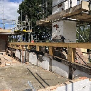 Looking over a roof of a fire damaged thatch cottage, currently being supported by lots of scaffolding, a new oak support has been installed along one side of the roof, this will support the new thatch coming soon. Communion Architects, Herefordshire, Worcestershire