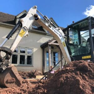A small digger with a white arm on site. The bucket rests on the floor behind the pile of earth in the foreground, a two storey White cottage in the background. On Site for an extension in Worcestershire, communion architects.