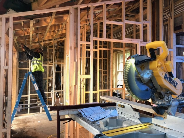 A builder in a high viz jacket in the back ground surrounded by a timber frame structure he is creating for an extension, a circular saw sits in the foreground. Communion Architects, Hereford.