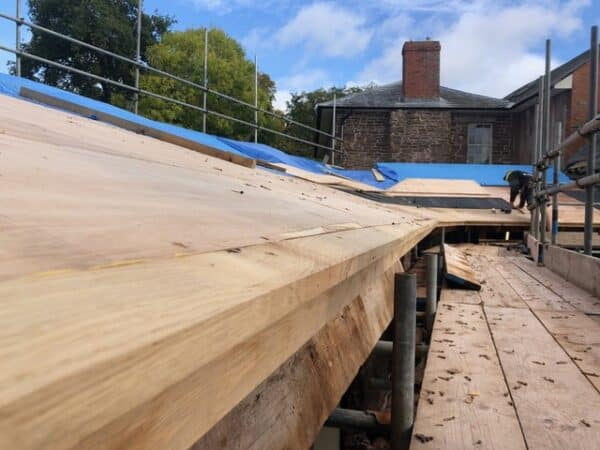Perspective image on a long wooden roof truss taking up most of the image, it leads the viewer to a stone build house in the background, the new roof truss is part of extension works on the site. Communion Architects, Hereford