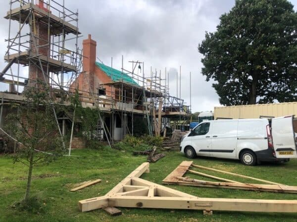 A wooden oak roof truss lays on green grass in the foreground, behind it is a white van and a red brick cottage covered with scaffolding. Communion Architects, Hereford.