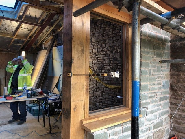 A new oak window frame set in a newly built stone wall, through the empty window a builder in a hi-viz jacket and white hard hat can be seen surveying works. Communion Architects, Hereford.