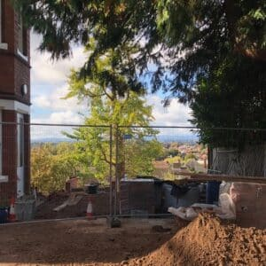 On the left hand side is a red brick victorian house with large windows, on the far right side is dark green foliage, in the centre, there is a cityscape view across Herefordshire partially blocked by a green tree in the centre. Communion Architects, Hereford.