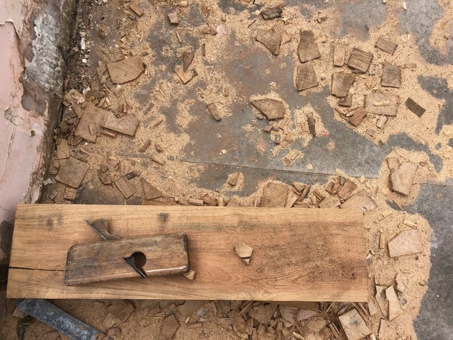 a short plank on wood laying on a grey concrete floor across the lower third of the image, the short plank is surrounded by wood chips, off cuts and saw dust. Communion Architects, Herefordshire.