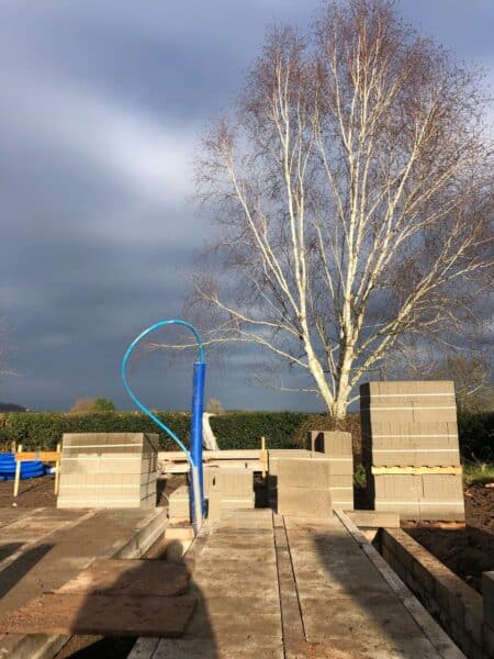 Concrete slabs laid on a new floor for a new dwelling occupy the lower third of the image, the middle third show shows piles of more concrete slabs while a grey and blue winter sky rises up in the background. Communion Architects, Herefordshire