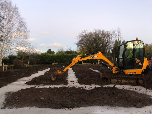 A small yellow digger with an extended arm reaching across a muddy ground. The ground is mostly mud with some poured concrete lines in a rectangular formulation, constituting the beginning of some foundations for a new house. Communion Architects, Hereford.