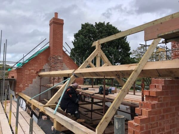 New oak roof truss partway completed on a red brick cottage, image taken from the scaffolding level with the roof trusses. Communion Architects, Hereford.