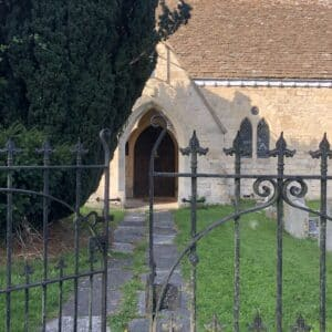 A wrought iron gate with one side slightly open. Behind the gate is a grassy graveyard and stoney path leading to the main door of a village church behind. The stone walls are a light yellow stone and the roof is pale brown. The church is partially obstructed by a large evergreen. Communion Architects, Hereford.