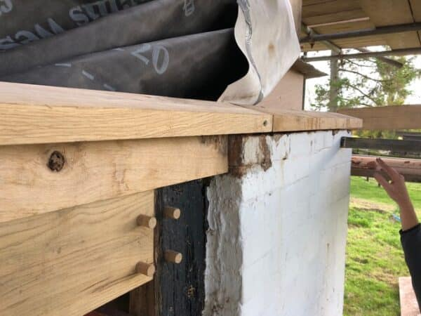 Close up of roof detailing a new oak beam connected with wooden pegs to an older wooden post which in turn is connected to a white washed stone wall. Communion Architects, Hereford.