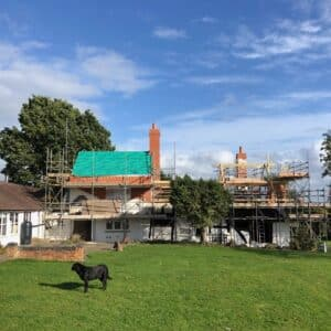 a old white washed cottage covered in scaffolding with a new roof in the process of being installed. Blue sky above and green grass below. Communion Architects, Hereford.