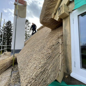 Close up of thatched roof and thatch dormer window. Image focuses on the thickness of thatch which is approximately 50 cm, based on sight. Communion Architects, Hereford, Herefordshire.