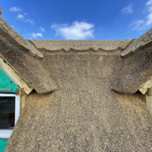 Two dormer windows with thatch and decorative ridges at the apex of the dormers and roof. Communion Architects, Hereford, Herefordshire.