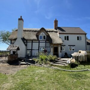 A black and white timber framed house with a thatched roof and large chimney breast on the left hand side. The right hand side has a double height extension with small windows, white render and tile roof, with grass in front. Communion Architects, Hereford, Herefordshire.