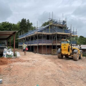 a muddy building site with Herefordshire's red clay soil. In the middle of the dirt is a scaffold-covered bungalow, a new dwelling. A yellow digger rests in front of the new house under construction. Communion Architects, Hereford, Herefordshire.