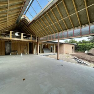 Interior of a new dwelling in Herefordshire, under construction. Concrete floor, timber beams, exposed insulation, in the pitched roof. The pitched roof has a pitched window running the length of the peak. The walls show exposed breeze blocks and brick, with the right hand wall open for floor to ceiling windows. Communion Architects Hereford.
