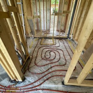 Timber framed wall building, part way through construction, with no packing between the timber frames yet. On the floor is a curling red tube curling across the floor expanse - part of an underfloor heating system. communion Architects Hereford, Herefordshire.