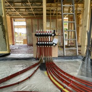 A timber framed structure under construction. at the centre of the image is a ground source heat pump with several red wires spreading out from it across the floor. Communion Architects Hereford, Herefordshire.