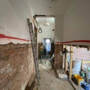 A corridor strewn with building equipment such as tool boxes and ladders. The top half of the walls are painted white, the lower half have been stripped and show exposed brick. A red line runs between the two. Communion Architects Hereford.