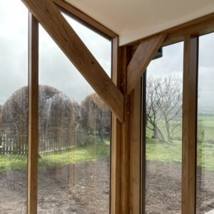 A portrait image of a corner of a room where two floor to ceiling windows meet with oak beam framing and bracing the space. cream roof and garden outside with a miuddy flower bed, grass and trees beyond. Communion Architects, Hereford, Herefordshire.