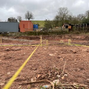 A muddy field, red Herefordshire clay soil, with yellow rope marking out rectangular zones. Preparing to dig foundations. Communion Architects, Hereford, Herefordshire.