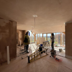 A freshly plastered room, light brown, still slightly damp. Two people stand in the space looking at the room and out the end window, the far wall has floor to ceiling glass windows looking out to a green grassy view. A new extension by communion architects, Hereford, Herefordshire.